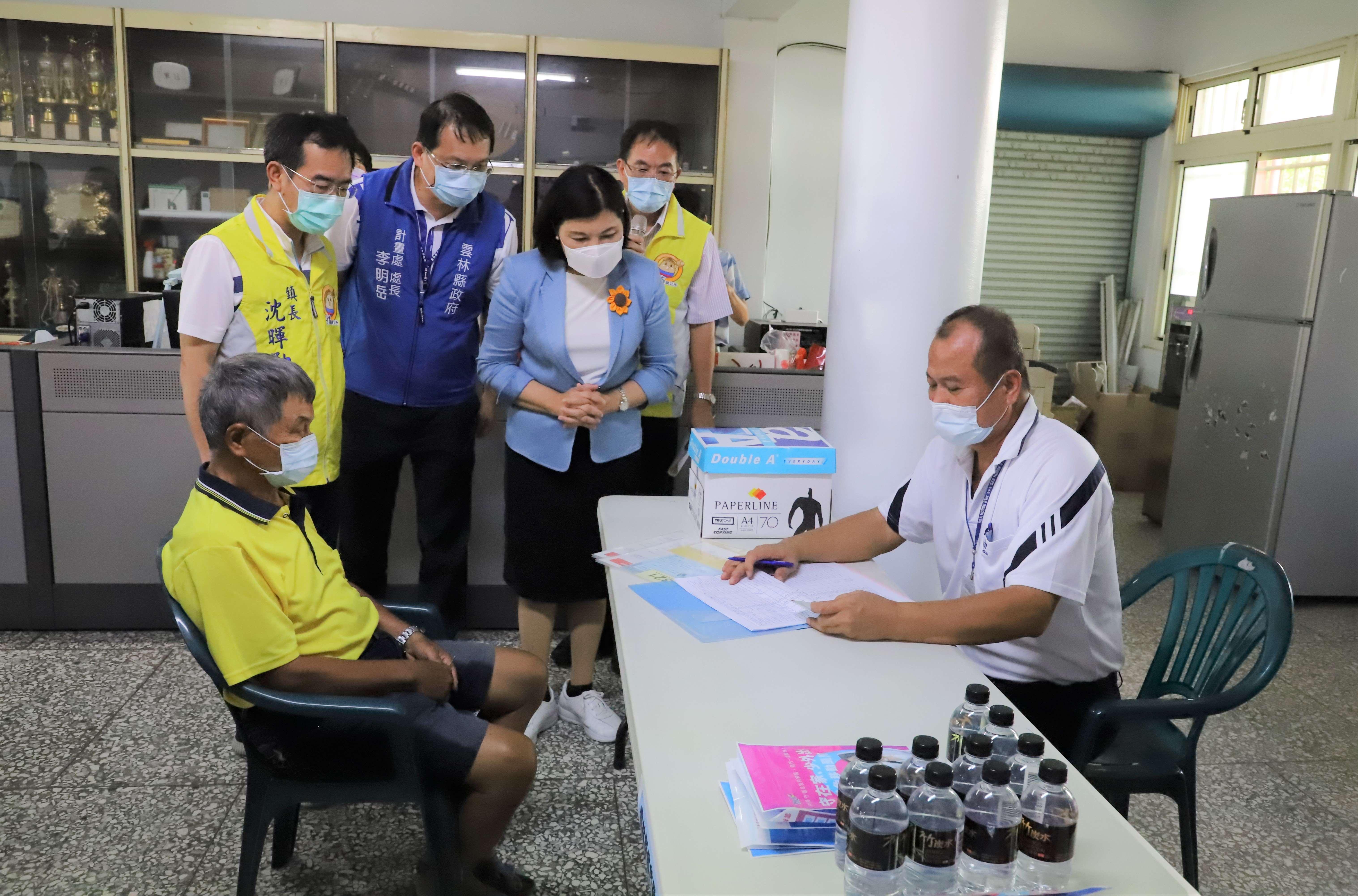 張縣長至斗南鎮新光里視察疫苗服務團協助長輩登記情形。